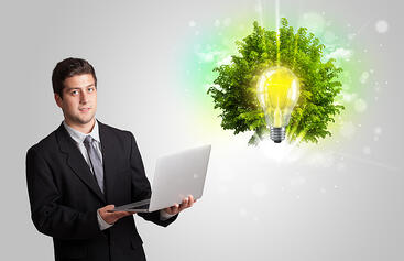 Young man presenting idea light bulb with green tree concept