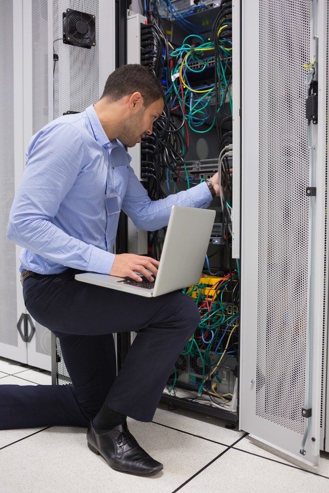 Man fixing wires during it field services job in houston